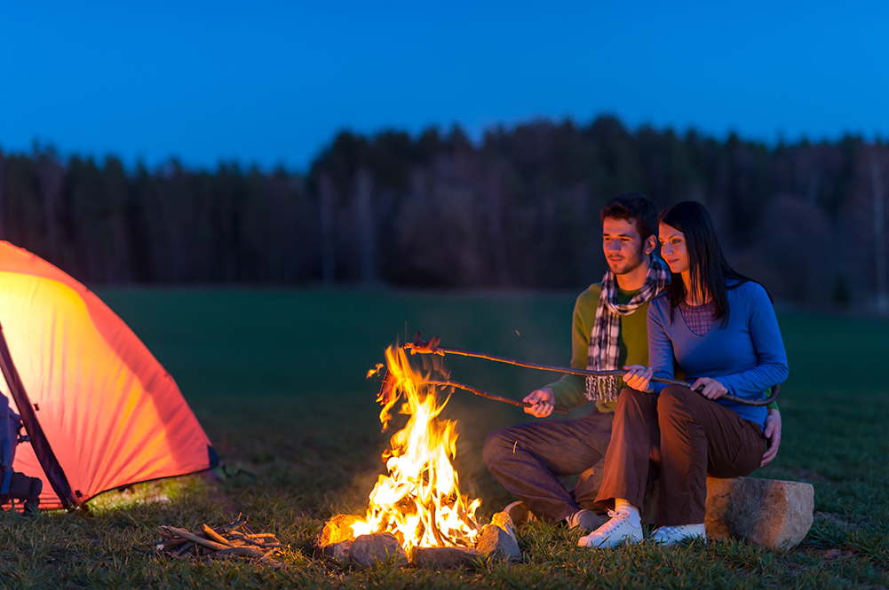Couple roasting marshmallows over campfire